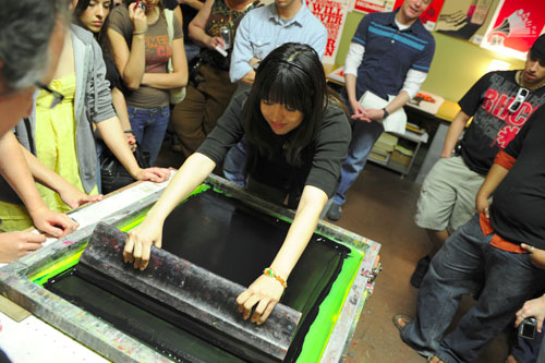 The other poster winner, Leah Ortega, prints the second color.